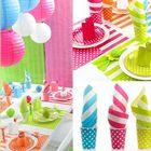 Vaisselle jetable, gobelet, serviette à pois et rayures multicolores.