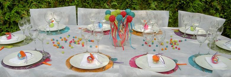 Décoration de table de baptême multicolore.